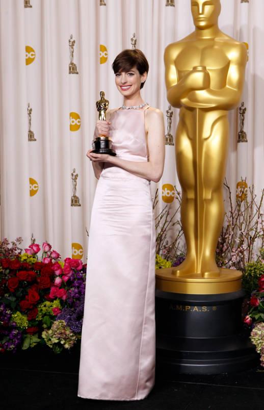 Anne Hathaway de Prada mostrando su estatuilla