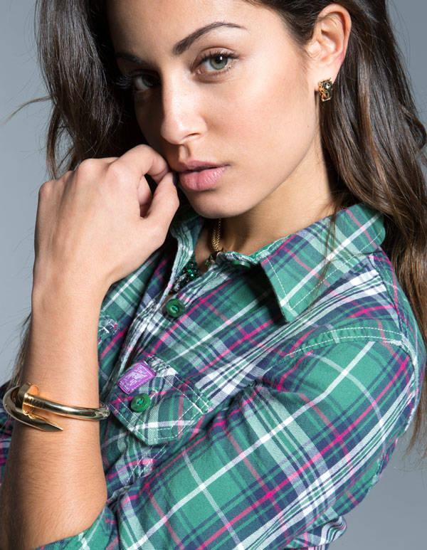 La actiz Hiba Abouk con camisa verde de cuadros de SUPERDRY, pulsera y pendienes de CARTIER y collar de SHOUROUK para MUÏC