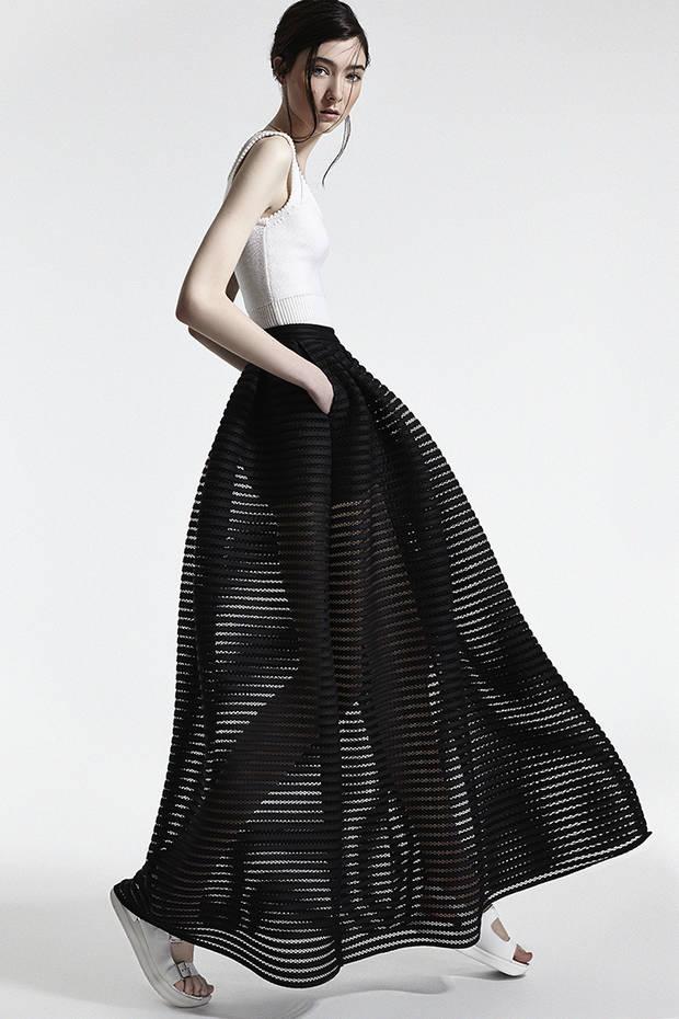 Top blanco CHRISTIAN DIOR Falda negra con vuelo y transparencias MAJE Sandalias planas blancas HOGAN